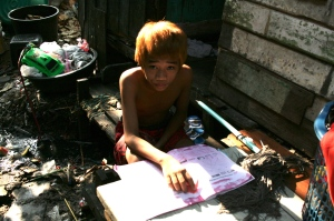 Chun, 13, lives in a squatter camp with his family. He quit school this year to work the streets to support his large family. Bangkok/ May 2014