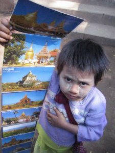 A child works to sell photographs in Yangon, Myanmar/ Dana MacLean.